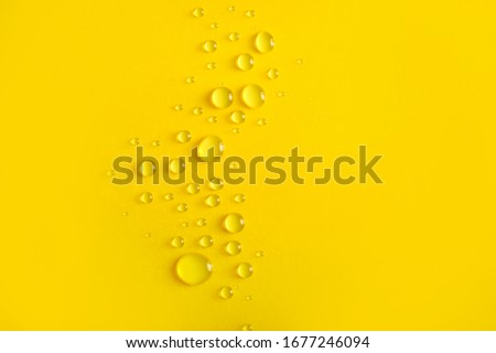 Water drops on yellow background Royalty-Free Stock Photo #1677246094