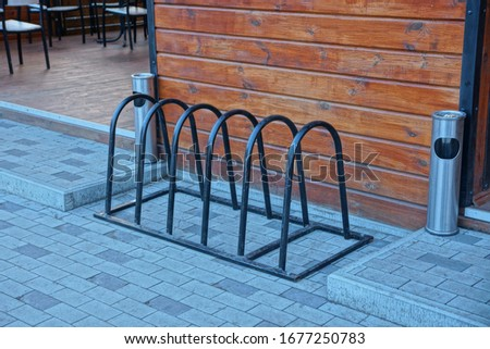 black iron bicycle parking stands on a gray sidewalk near a brown wooden wall with metal urns #1677250783
