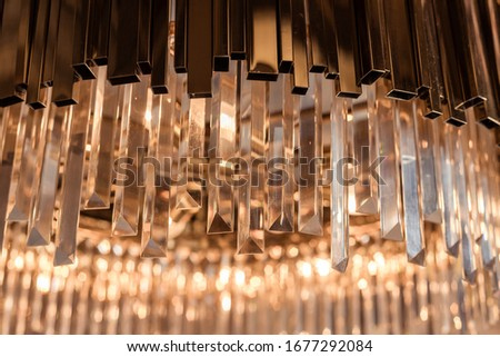 Golden bohemian background of crystal pendants on the chandelier. Shallow depth of field, close-up, picture with bokeh