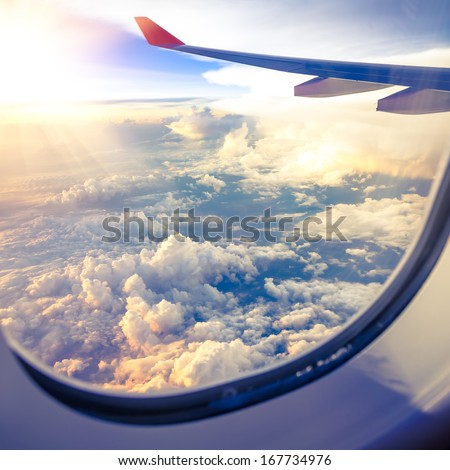 Clouds and sky as seen through window of an aircraft Royalty-Free Stock Photo #167734976