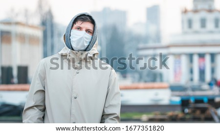 Close-up portrait young europeans man in protective disposable medical face mask walking outdoors. New coronavirus (COVID-19). Concept of health care during an epidemic or pandemic #1677351820