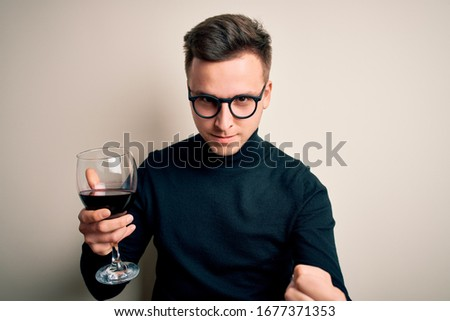 Young handsome caucasian man drinking an alcoholic glass of red wine over isolated background annoyed and frustrated shouting with anger, crazy and yelling with raised hand, anger concept #1677371353