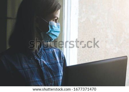 Woman in medical mask is working from home. Online freelance during the time of quarantine. Laptop in hands near the window. Coronavirus pandemia. Economics crisis alternatives. #1677371470
