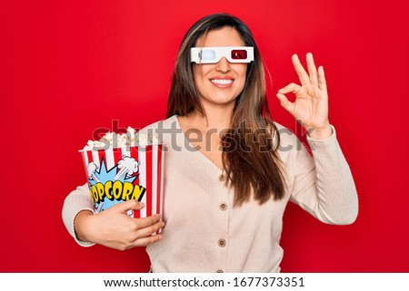 Young hispanic woman wearing 3d movie glasses and eating popcorn over red background doing ok sign with fingers, excellent symbol #1677373351