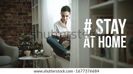 Young woman isolating at home and relaxing, she is reading a book: stay at home social media campaign for coronavirus prevention #1677376684
