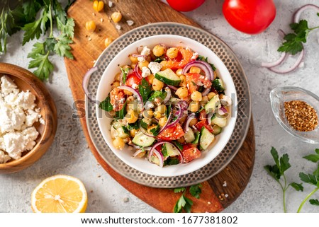 Chickpea salad with tomatoes, cucumber, feta cheese, parsley, onions and lemon in a plate on a gray background top view, selective focus. Healthy vegetarian food, oriental and Mediterranean cuisine. Royalty-Free Stock Photo #1677381802