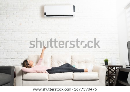 Full length of Latin young woman turning on mini split while relaxing on sofa at home Royalty-Free Stock Photo #1677390475