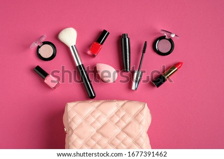 Makeup bag with cosmetic products spilling out on to pastel pink background. Flat lay, top view. Stylish make up artist pouch with professional beauty products #1677391462