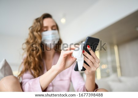 European woman in face mask cleaning the phone by hand sanitizer, using cotton wool with alcohol to wipe to avoid contaminating with Corona virus. Cleaning mobile phone to eliminate germs, Covid-19.  #1677398488