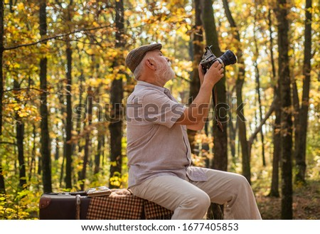Shooting autumn session. Old man shoot in nature. Landscape and nature photo shooting. Using handheld shooting. Hobby and lifestyle. Shooting, filming and camerawork. Fall photoshoot.