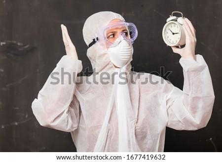 female doctor in protection suit and glasses with mask holds alarm clock  #1677419632