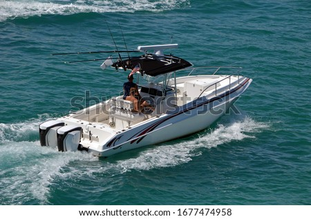 Small open white fishing boat with center console cruising the Florida Intra-Coastal Waterway off Miami Beach. Royalty-Free Stock Photo #1677474958