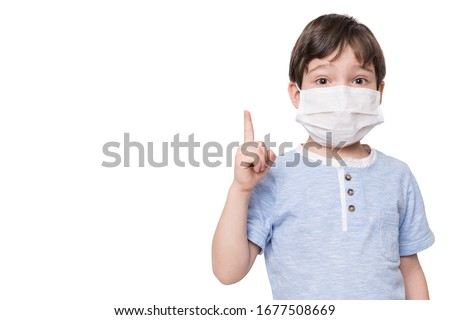 Portrait of kid with face mask pointing finger up, isolated on white background #1677508669