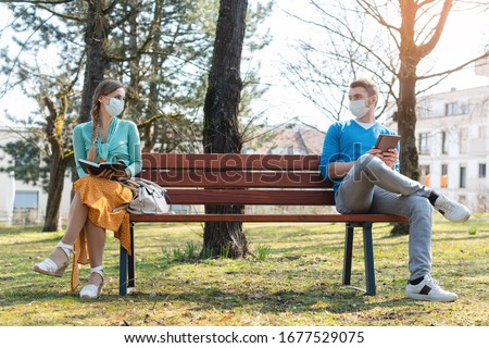 Woman and man in social distancing sitting on bench in park #1677529075