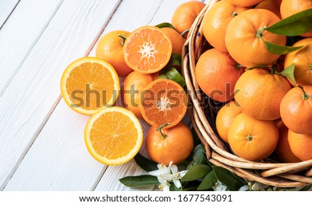 Orange fruit with green leaves on the white wood.  Home gardening. Mandarine oranges. Tangerine  oranges. Orange color. Fresh orange juice. #1677543091