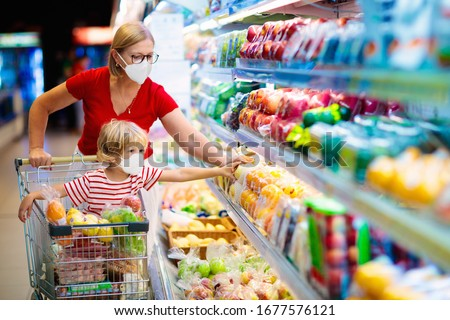 Shopping with kids during virus outbreak. Mother and child wearing surgical face mask buying fruit in supermarket. Mom and little boy buy fresh vegetable in grocery store. Family in shop.  Royalty-Free Stock Photo #1677576121