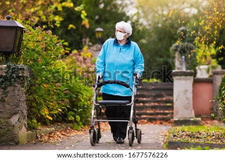 Senior handicapped lady wearing face mask with a walking disability at coronavirus outbreak. Old person in surgical mask pushing walker or wheel chair. Disabled sick patient of nursing home. #1677576226