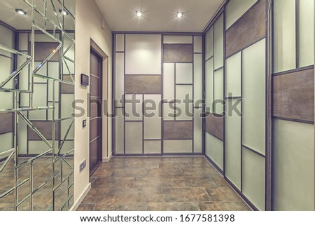 Empty residential house entrance with closed doors build in closets with mirrors #1677581398