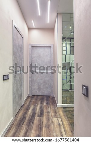Empty residential house entrance with closed doors build in closets with mirrors #1677581404