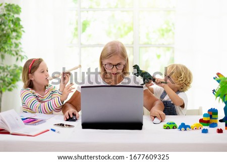 Mother working from home with kids. Quarantine and closed school during coronavirus outbreak. Children make noise and disturb woman at work. Homeschooling and freelance job. Boy and girl playing. #1677609325