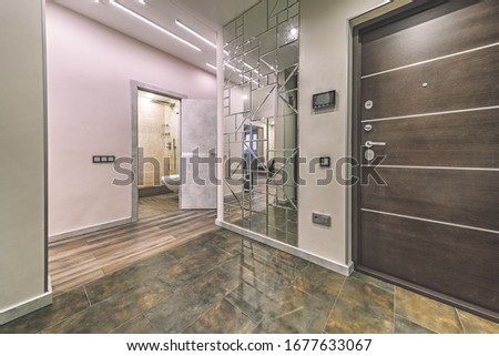 Empty residential house entrance with closed doors build in closets with mirrors #1677633067