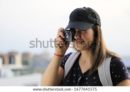Young female tourist with a black baseball cap taking a picture with a first generation digital camera