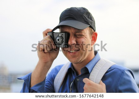 Young male tourist with a black baseball cap taking a picture with a first generation digital camera