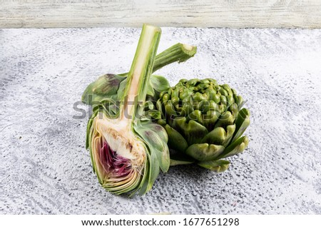 High angle view artichokes and a slice on gray wooden background. horizontal #1677651298