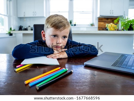 Coronavirus Outbreak. Lockdown and school closures. School boy with face mask watching online education classes feeling bored and depressed at home. COVID-19 pandemic forces children online learning. #1677668596