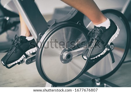 Fitness machine at home woman biking on indoor cycling stationary bike exercise indoors for cardio workout. Closeup of shoes on bicycle. Royalty-Free Stock Photo #1677676807
