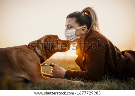 Woman wearing a protective mask is walking alone with a dog outdoors because of the corona virus pandemic covid-19 #1677729985