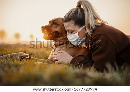Woman wearing a protective mask is walking alone with a dog outdoors because of the corona virus pandemic covid-19 #1677729994