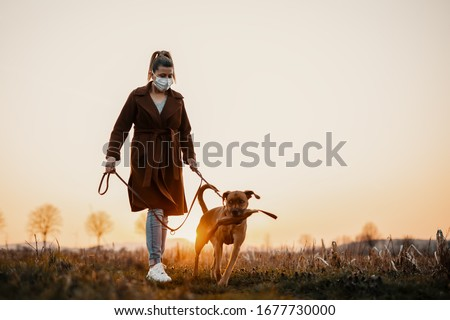 Woman wearing a protective mask is walking alone with a dog outdoors because of the corona virus pandemic covid-19 Royalty-Free Stock Photo #1677730000