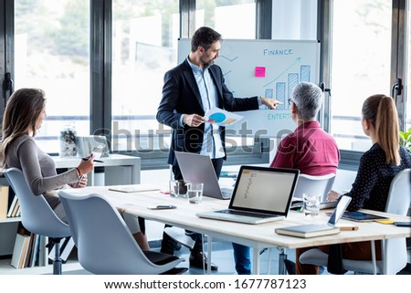 Shot of handsome businessman explaining a project to his colleagues on coworking place. Royalty-Free Stock Photo #1677787123