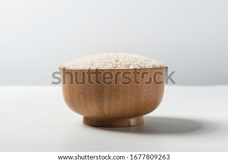 Rice in a wooden bowl isolated under a straw mat on a white background. Tile (top) #1677809263
