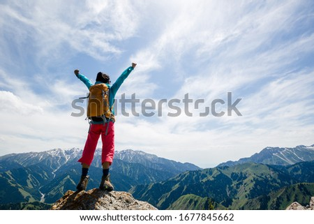 Strong woman hiker outstretched arms stand at cliff edge on mountain top Royalty-Free Stock Photo #1677845662