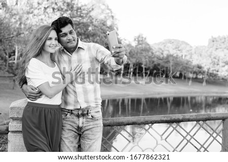 Happy multi ethnic couple smiling and in love while taking selfie picture with mobile phone together on the bridge of peaceful green park