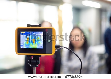 Asian people waiting for body temperature check before access to building for against epidemic flu covid19 or corona virus from wuhan in office by thermoscan or infrared thermal camera #1677868924