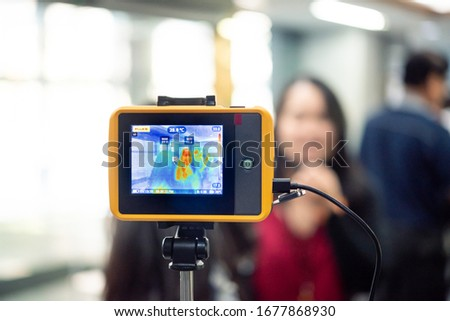 Asian people waiting for body temperature check before access to building for against epidemic flu covid19 or corona virus from wuhan in office by thermoscan or infrared thermal camera #1677868930