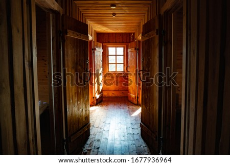 Wooden house hallway picture. Light coming from the window at the end. Sunny weather outside. Bed rooms on the sides. Doors open. Timber construction. Log cabing. Wooden flooring.