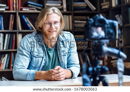 Smiling young male creator blogger influencer talking looking at professional dslr digital camera shoot education tutorial vlog training filming video course for social media sit at desk in library.