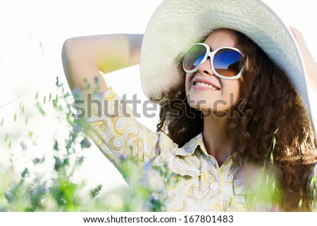 Young beautiful girl in hat and glasses sitting in grass #167801483