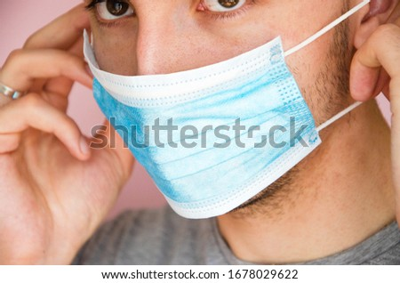 A man in a gray T-shirt on a pink background puts on a medical blue mask on his face. Virus protection.  COVID-19 #1678029622