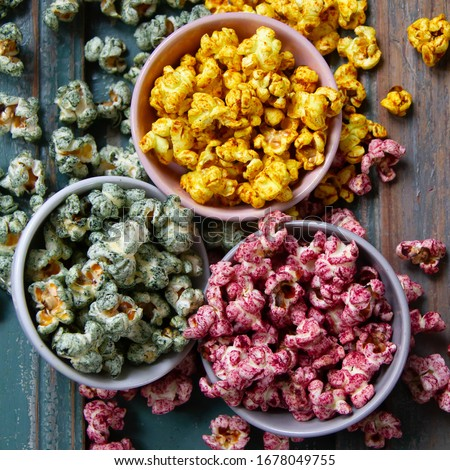 Food photography of pink, yellow and green popcorns on dark green wooden board