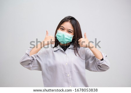 Portrait of a cheerful and healthy young woman asian wearing medical mask. Pandemic 2019 Coronavirus 2019-nCoV Concept. #1678053838