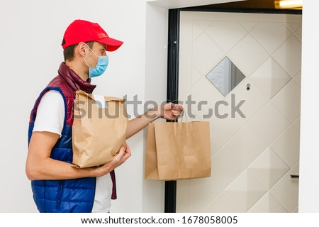 Delivery man holding paper bag with food on white background, food delivery man in protective mask #1678058005
