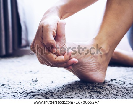 person with foot pain and nerve inflammation and foot bone, heel, and joint pain use hand massage to treatment of numb toes.