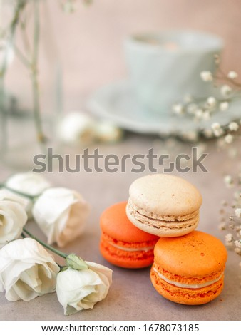 Macaroons cakes and white rose flowers and a Morning cup of coffee on light gray stone table background. Beautiful breakfast. Selective focus. Vertical image