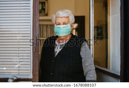 Old woman with mask isolated at home standing on her front doors and waiting for groceries #1678088107