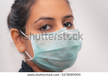 Indian woman wearing a protective surgical mask for COVID-19 coronavirus Pandemic #1678089004